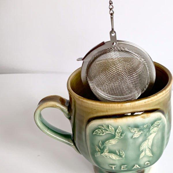 Metal tea infuser going into tea cup.