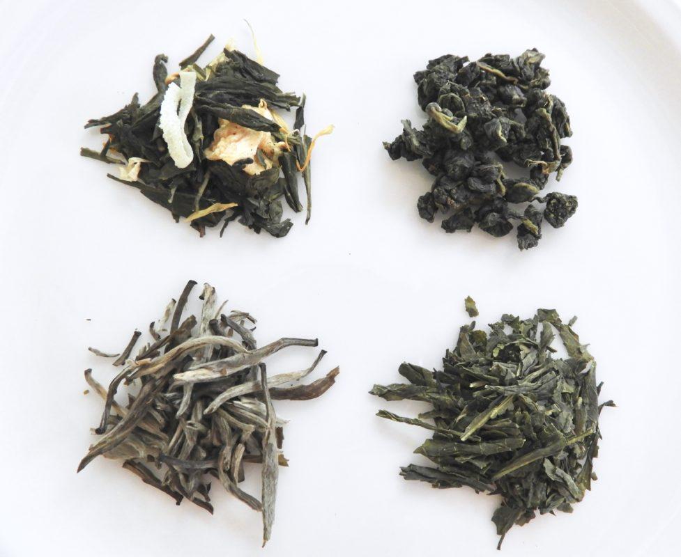 Loose leaf tea samples on white background.